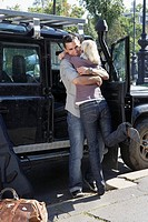 Couple embracing by an SUV smiling (thumbnail)