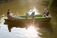 Four friends in a rowboat smiling and relaxing