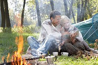 Couple sitting at campsite looking at map by the fire smiling
