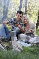 Couple at campsite cooking hot dogs and smiling
