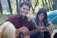 Man at campsite playing guitar with two woman listening and smiling