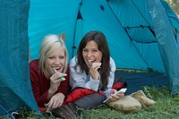 Two women at campsite brushing teeth in tent and smiling