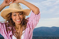 Woman laughing and wearing a hat outdoors
