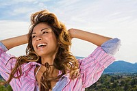 Woman smiling with hands behind head outdoors