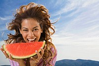 Woman laughing and eating watermelon outdoors
