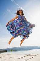 Woman jumping by an infinity pool in a colorful dress smiling