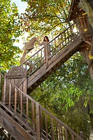 Woman climbs wood outdoor stairway holding blanket