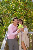 Couple standing on balcony holding leaf smiling