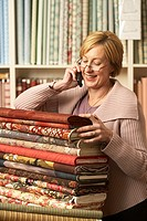 Mature woman talking on phone leaning on pile of rolled up textiles