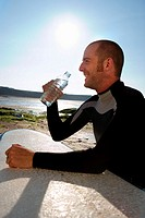 Man sitting with surfboard drinking water smiling