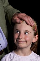 Grandfather holding hand on granddaughter´s 8-9 forehead, close-up of girl