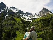 Couple embracing, looking at mountains, rear view