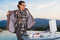 Woman putting on jacket while working at home outdoors