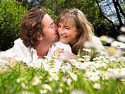 Couple lying in the grass smiling and kissing