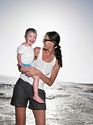 Woman holding a young girl at the beach smiling