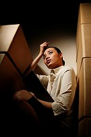 Businesswoman hiding in between big boxes scratching her head