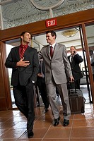 Business men with suitcases walking in hotel foyer, low angle view