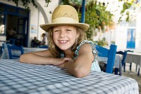 Young girl at an outdoor restaurant smiling