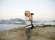 Young boy using binoculars in Greece