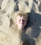 Young boy buried in the sand smiling