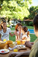 ´Family, including daughter 6-7 sitting at table in garden, smiling´