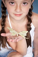 Girl 6-7 with butterfly on hand, portrait