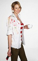 Woman holding paintbrush and tea cup, portrait, studio shot