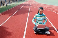 Girl sitting on the sports track using laptop