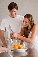 A couple making orange juice