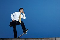 Businessman talking on the phone and holding briefcase while standing on a skateboard
