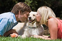 Man and woman kissing dog