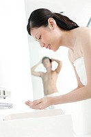 Woman washing her face while husband is taking a shower