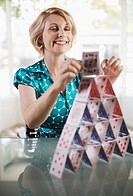 Smiling businesswoman building house of cards