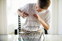 Boy building house of cards