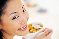 Woman smiling at the camera while enjoying her breakfast cereal