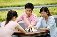 Women playing chess game, man watching