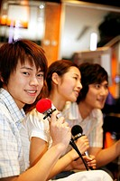 Men and woman singing together in karaoke bar