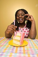 Girl 10-11 talking on mobile phone, sticking fork into slice of cake, studio shot