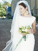 Bride standing with bouquet outside church