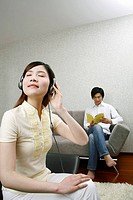 Woman wearing headphones with man in the background reading book