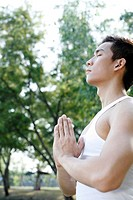 Man practising yoga in the park