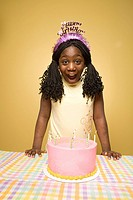 Girl 10-11 wearing party hat, standing over birthday cake, studio shot