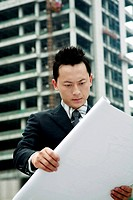Businessman looking at building plan