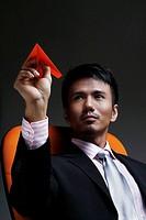Businessman holding a paper plane