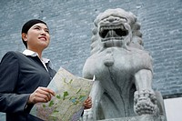 Businesswoman standing next to a lion statue, holding a map