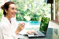 Woman holding a cup of coffee while using laptop