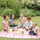 Five children 8-11 having picnic in garden