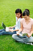 Students reading book and using laptop