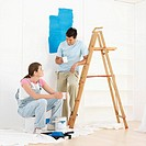 Couple taking break from painting wall in home