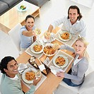 Two couples eating meal at living room table, portrait